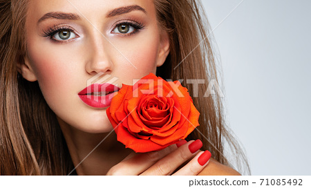 Beautiful young woman with a red flower in hand near face.  Portrait of a  girl with red rose in hands 71085492