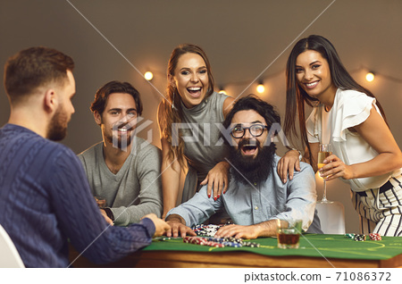 Excited winner sitting at poker table surrounded by happy friends drinking and celebrating victory 71086372