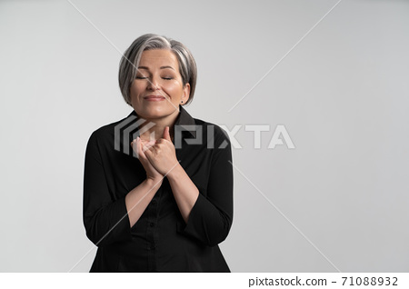 Happy mature woman folded hands with closed eyes on white background. Dreams concept. Emotions concept 71088932