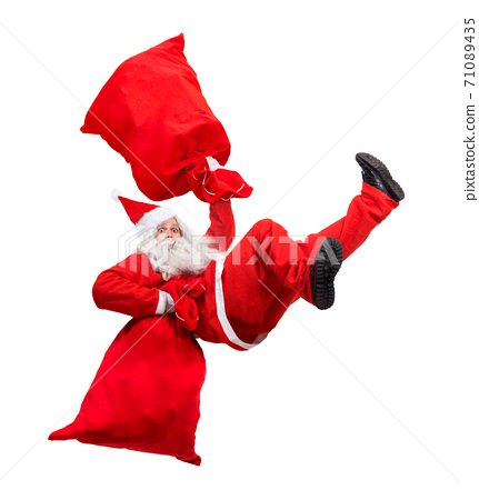 Funny Santa Claus falls with a bag full of x-mas gifts.  71089435