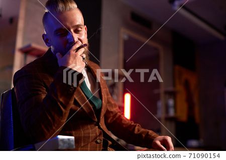 confident wealthy male in suit sit smoking cigar 71090154