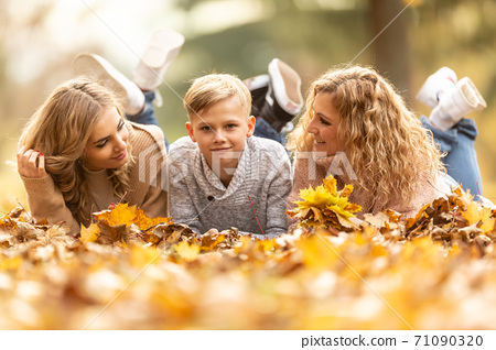 Blonde family of mother, teenage girl and boy lie down on a foliage enjoying good times together 71090320