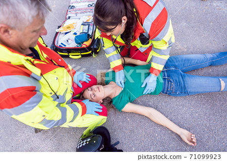 Paramedic and emergency doctor at site of traffic accident 71099923