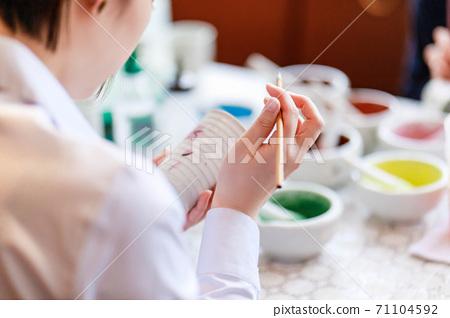 一位年輕女子正在陶器繪畫 71104592
