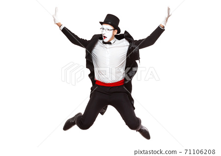 Portrait of a male mime artist performing, isolated on white background. Jumps high with his hands up. A symbol of joy and good mood 71106208