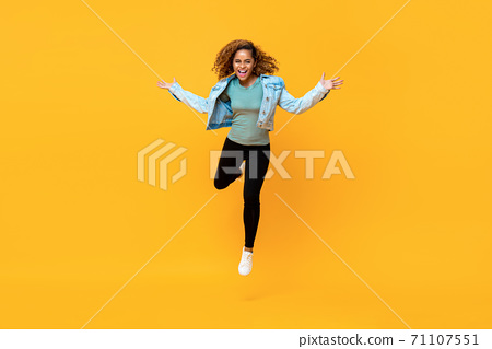 Energetic young African American woman jumping while arms outstretched 71107551