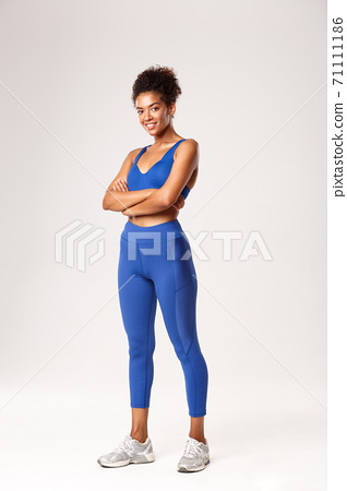 Full length of confident african-american sportswoman smiling pleased at camera, cross arms on chest and looking at camera, wearing sportswear for workout or gym exercises, white background 71111186