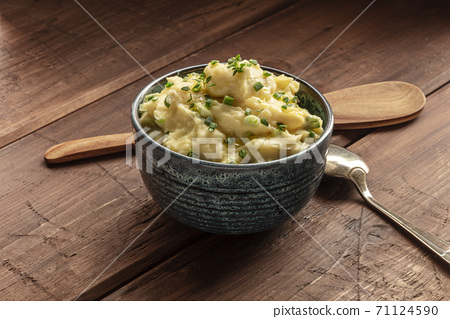 Pomme puree, a photo of a bowl of mashed potatoes with herbs on a rustic background with a wooden spoon 71124590