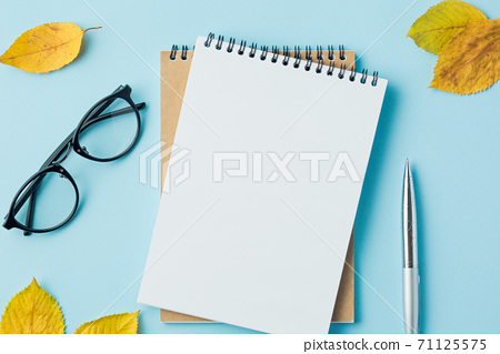 notebook on blue table top view, with blank page 71125575