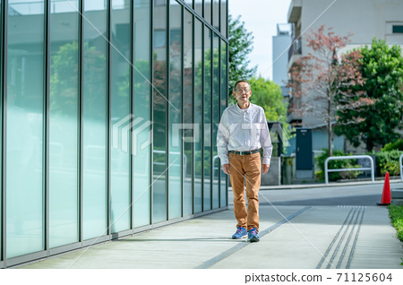 Senior man walking with a smartphone 71125604