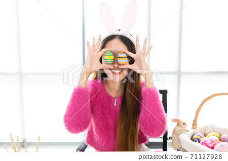 Happy smile Asian Young woman wearing bunny ears and holding up a colorful Easter egg in front of her eye Skewers In the white room background 71127928