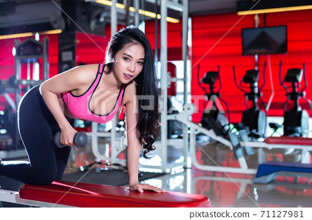 Fitness Asian women performing doing exercises training with dumbbell sport in sport gym interior and fitness health club with sports exercise equipment background. 71127981