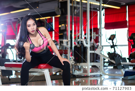 Fitness Asian women performing doing exercises training with dumbbell sport in sport gym interior and fitness health club with sports exercise equipment background. 71127983