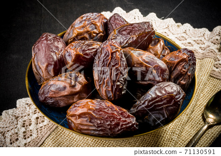 Big luxury dried date fruit in bowls on a linen napkin, kurma ramadan kareem concept, close up. 71130591