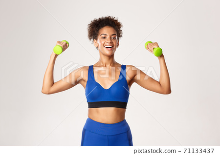 Concept of sport and workout. Strong and fit african-american fitness woman in blue gym clothing, exercising with dumbbells, standing against white background 71133437
