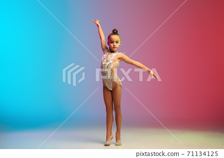Little caucasian girl, rhytmic gymnast training, performing isolated on gradient blue-red studio background in neon 71134125