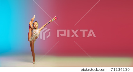 Little caucasian girl, rhytmic gymnast training, performing isolated on gradient blue-red studio background in neon 71134150