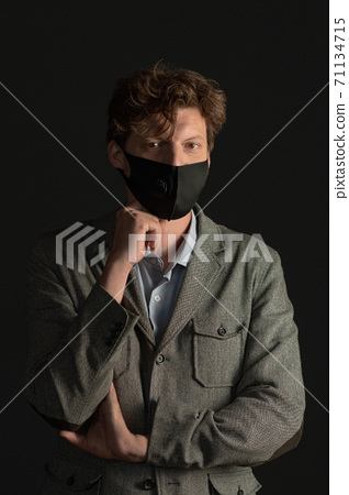 Masked business man looks seriously with his chin on his fist. Studio portrait. Black background 71134715
