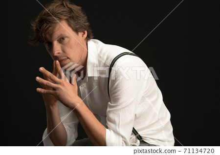 Serious thoughtful man sits in thinking position. Shaggy Caucasian guy wearing a white shirt and suspenders isolated on black background with copy space at right. 71134720