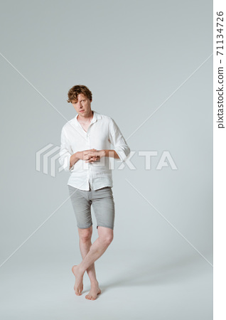 Pensive man standing full length folded arms and crossed legs. Thinking barefoot male model in white shirt demonstrates his emotions while posing on white background.  71134726