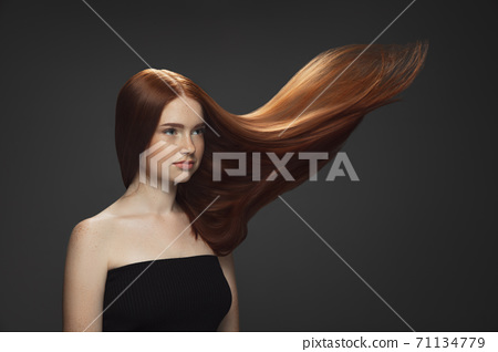 Beautiful model with long smooth, flying red hair isolated on dark studio background. 71134779