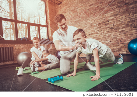 Dad teaches son to stand in the plank in the gym.  71135001