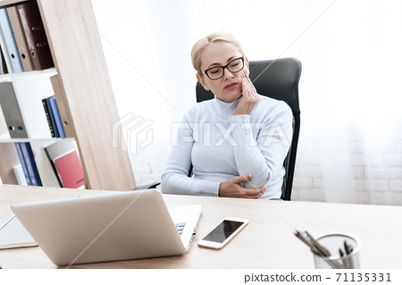 A woman sits at a desk and feels a toothache.  71135331