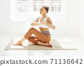 Back view of unrecognizable female in sportswear sitting with crossed legs and mudra hands on mat and doing yoga while practicing mindfulness 71136642