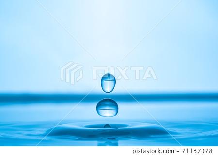 Water drop splashing into blue water surface 71137078
