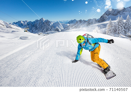 Snowboarder going downhill in high mountains 71140507