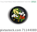 Feta and Mozzarella cheese with vegetables on a black plate. 71144089