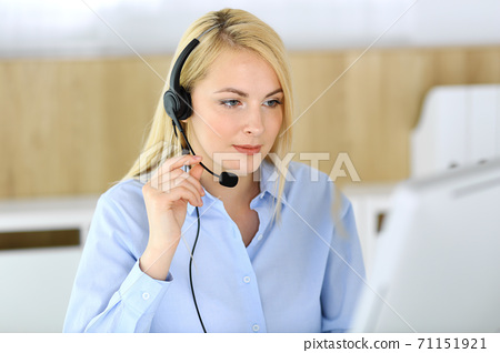 Call center. Blonde business woman sitting in headset at customer service office. Concept of telesales business or home office occupation 71151921