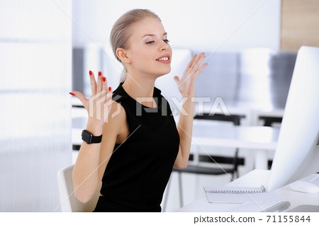 Business woman happy and excited while working with computer in modern office. Secretary or female lawyer looks beautiful in black dress. Raised arms because of emotion. Business people concept 71155844
