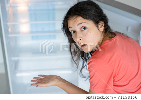 The girl is surprised at the empty refrigerator. Lack of food. Food delivery 71158156