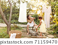 Mother and daughter hanging laundry in backyard 71159470