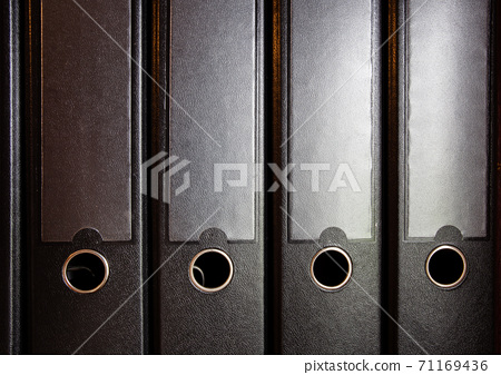 four black ring binders on a bookshelf for office or administration, business concept background 71169436