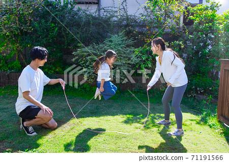 一個好朋友家庭在花園裡跳繩玩 71191566