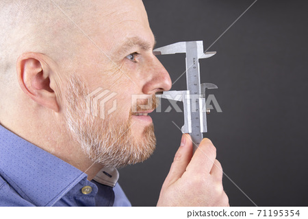 man measures the size of his nose measuring device caliper 71195354