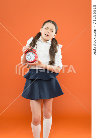 School alarm. Happy girl hold alarm clock counting for lunch time. School time 71196818