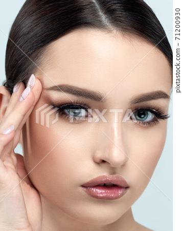 Young beautiful woman touching her face 71200930
