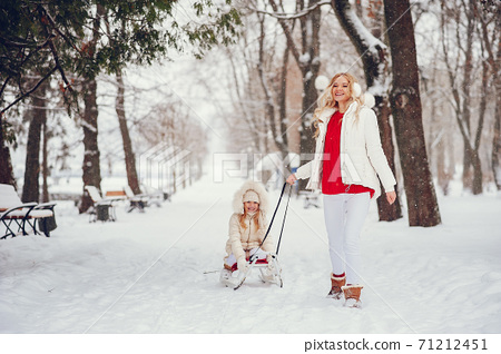 Mother and daughter in a winter park 71212451