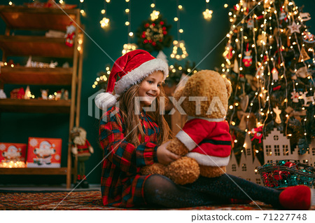 Portrait of cutel little child girl playing with Taddy bear, New year holiday concept 71227748