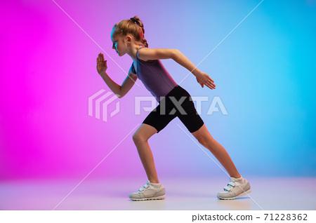 Teenage girl running, jogging against gradient pink-blue neon studio background in motion 71228362