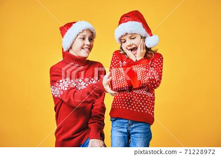 Boy handing Christmas present to surprised girl 71228972