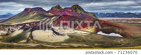 Panoramic surreal magic Icelandic landscape of colorful rainbow volcanic Landmannalaugar mountains, red and pink volcanic crater Stutur at famous Laugavegur hiking trail with dramatic sky and a big 71236070