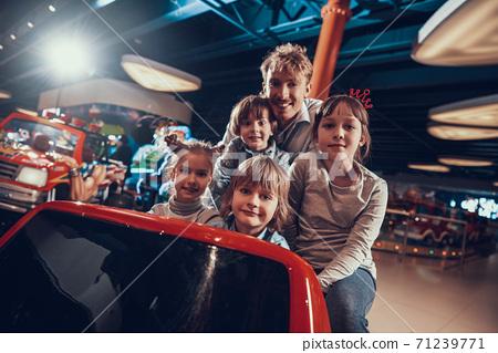 Cheerful children with dad in entertainment center 71239771