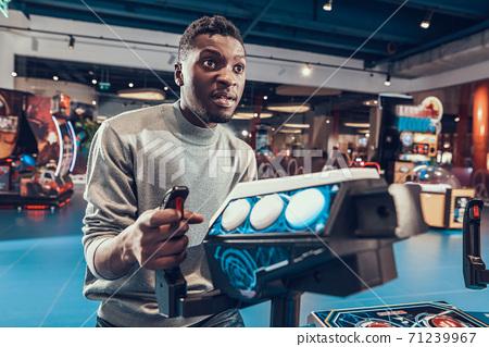African guy piloting spacecraft in arcade. 71239967