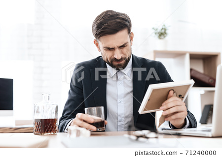 A man sits at table and holds frame with a photo. 71240000
