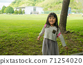 站立在草坪前面的一個微笑的女孩 71254020