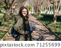 Intellectual young girl stays and look to someone in a park with some books in her hands. 71255699
